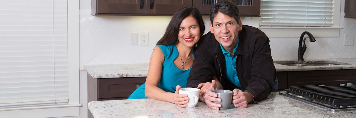 Couple smiling & leaning against white granite countertops renewed by Chem-Dry of Rialto