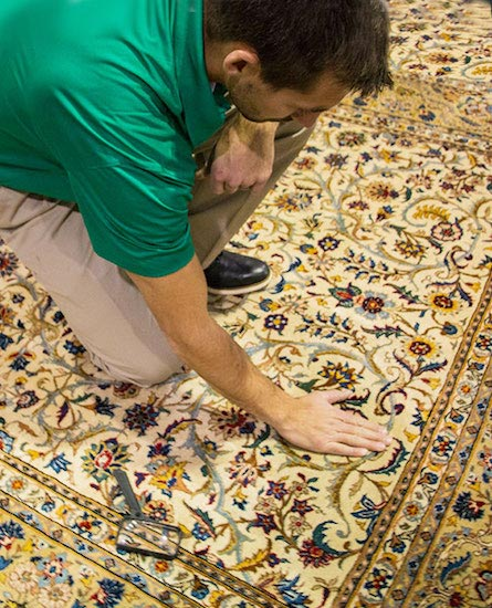 Chem-Dry technician evaluating area rug to determine the best method for safely cleaning it.